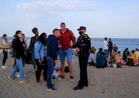 Polícia aborda pessoas em praia de Barcelona  2/4/2021   REUTERS/Nacho Doce
