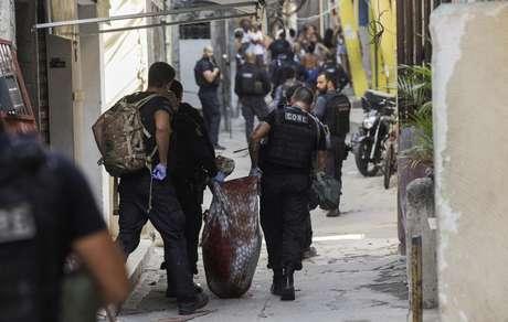 Policiais carregam corpo durante operação na favela do Jacarezinho