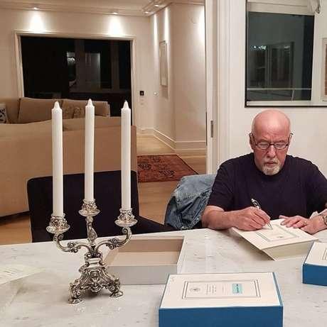 O imortal Paulo Coelho autografa livros em seu apartamento durante o lockdown na Suíça, ano passado