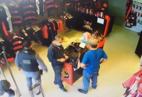 Momento em que policial entra na loja e cruza com idosos, que deixam o local em seguida (Foto: Reprodução)