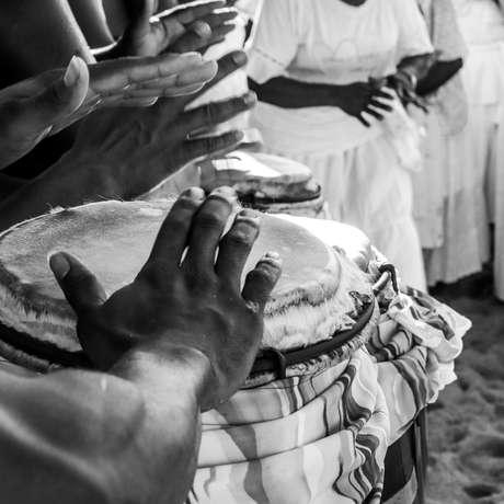 Homem toca atabaque em ritual de umbanda