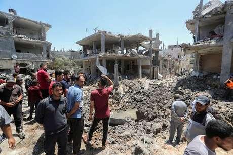 Palestinos se reúnem perto de casas destruídas por ataques aéreos e de artilharia de Israel no norte da Faixa de Gaza 14/05/2021 REUTERS/Mohammed Salem