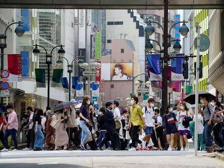Pedestres usam máscaras de proteção enquanto caminham sob rua decorada para os Jogos Olímpicos e Paralímpicos de Tóquio 2020, que foram adiados para 2021 devido à pandemia de Covid-19, em Tóquio, no Japão 14/05/2021 REUTERS/Naoki Ogura