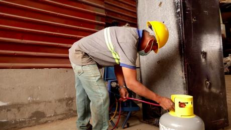 Um trabalhador da empresa de Toledo extrai gases refrigerantes de um eletrodoméstico antigo