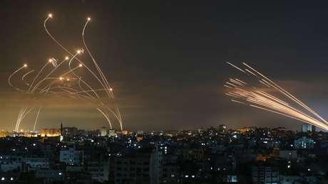 Os mísseis israelenses, à esquerda, lançados para interceptar os foguetes do Hamas, à direita