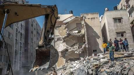 Palestinos inspecionam casa destruída, após ser atingida por ataques israelenses, na Cidade de Gaza, neste domingo
