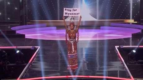 """Representante de Mianmar no concurso Miss Universo, Thuzar Wint Lwin, segura cartaz com os dizeres """"Orem por Mianmar"""" 13/05/2021 Cortesia MISS UNIVERSE/Divulgação via REUTERS"""