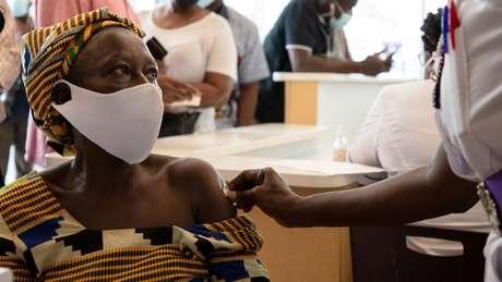 Mulher sendo vacinada em Gana, país que já utilizou 100% das doses de vacina recebidas do Covax
