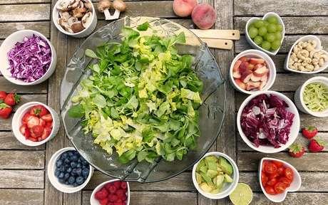 Alimentos ricos em nutrientes como saladas, frutas e verduras dispostos sobre um balcão. Os nutrientes são importantes dicas de alimentação para um organismo saudável