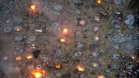 Na Índia, os crematórios têm recorrido a piras funerárias em massa à medida que o número de corpos de vítimas de covid continua aumentando