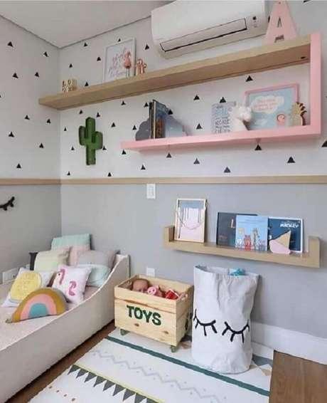 19. Almofada infantil personalizada e papel de parede de triângulos pretos decoram o quarto. Fonte: Stúdio 166