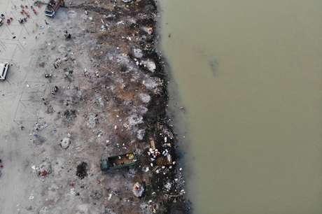 Foto de 5 de maio mostra pontos de cremação às margens do rio Ganges; é comum hindus cremarem seus mortos