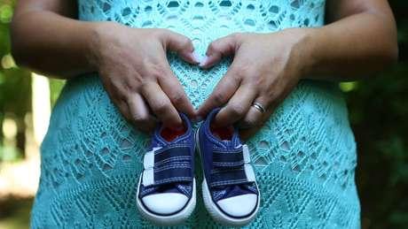 Barriga de grávida, que segura dois sapatinhos de bebê
