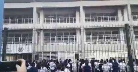 Vídeos divulgados nas redes sociais mostram estudantes aglomerados no pátio da escola, durante hasteamento de bandeiras