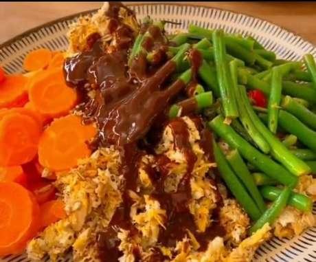 Café da manhã com ovos com aveia e frango, vagem, cenoura, abobrinha e molho barbecue.