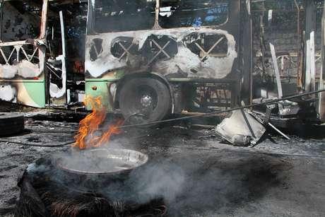 Funcionários de empresa de ônibus, trabalham para remover dois ônibus dos 14 que foram queimados por facções em ataques
