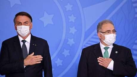 Jair Bolsonaro e Marcello Queiroga lado a lado com a mão no peito
