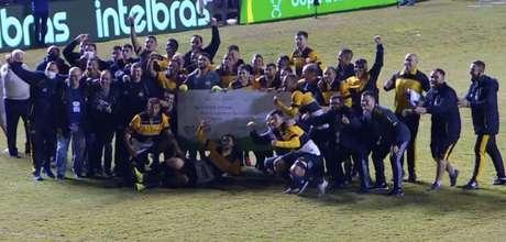 Jogadores do Criciúma comemoram classificação em cima do América Mineiro para as oitavas de final da Copa do Brasil com um cheque gigante de R$ 500 mil (Reprodução)