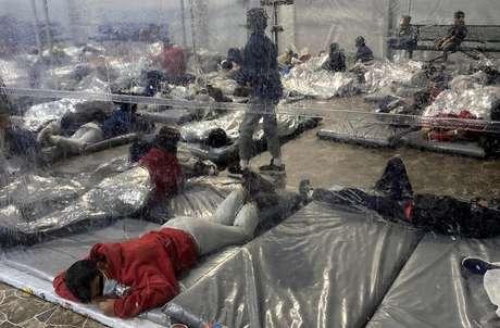 Jovens migrantes na instalação são mantidos em áreas lotadas separadas por lonas de plástico