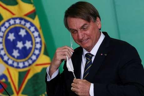 Presidente Jair Bolsonaro mexe na máscara durante cerimônia no Palácio do Planalto 10/06/2021 REUTERS/Adriano Machado