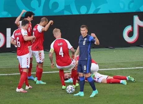 Jogador da Dinamarca Christian Eriksen, caído em campo, enquanto companheiros de equipe pedem socorro médico.  12/6/2021 Pool via REUTERS/Wolfgang Rattay