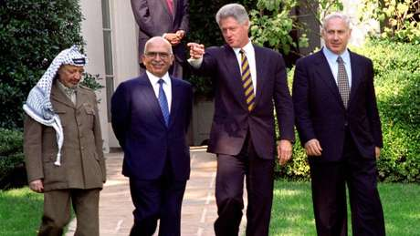 Mr Netanyahu (dir.) participou das conversas com líder palestino Yasser Arafat (esq.) e o Rei Hussein, da Jornânia (centro-esq.), com mediação do então presidente americano Bil Clinton (centro-dir.), em outubro de 1996