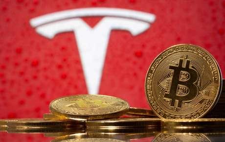 Representação da moeda virtual bitcoin tendo ao fundo o logotipo da montadora de veículos elétricos Tesla. 9/2/2021. REUTERS/Dado Ruvic