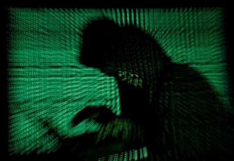 Imagem da silhueta de uma pessoa usando um laptop, tendo ao fundo códigos criptográficos. 13/5/2017.  REUTERS/Kacper Pempel