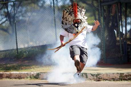 Líder indígena Kretan Kaingang chuta de volta bomba de gás lacrimogêneo lançada pela polícia contra indígenas durante protesto em frente ao Congresso