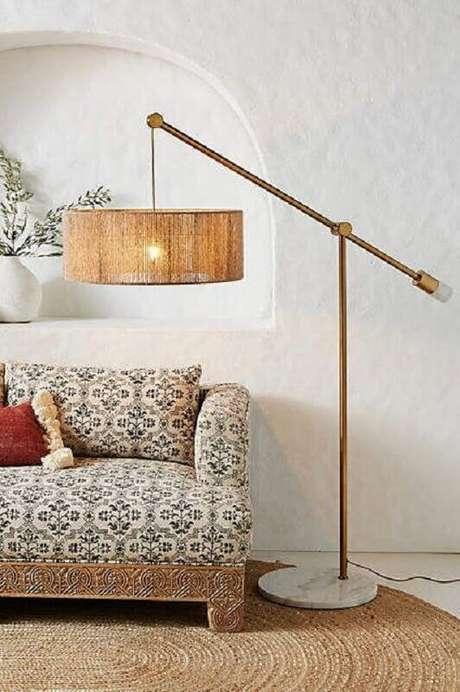 39. Decoração com abajur de pé rústico e sofá com estampa vintage – Foto: Anthropologie