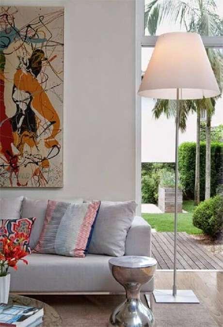 58. Sala de estar moderna decorada com quadro colorido e abajur de pé alto – Foto: Pinterest
