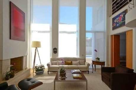 24. Abajur de pé para sala grande decorada com poltrona marrom e sofá bege – Foto: Jannini Sagarra Arquitetura