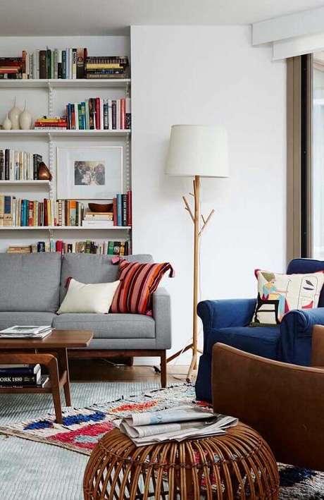 21. Abajur de pé para sala decorada com estante de livros e poltrona azul – Foto: Jeito de Casa