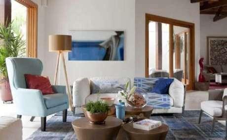 59. Sala decorada com poltrona azul pastel e abajur de pé alto de madeira – Foto: Deborah Roig