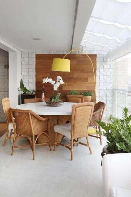 8. Abajur de pé amarelo para decoração de varanda branca com mesa redonda – Foto: Studio Novak