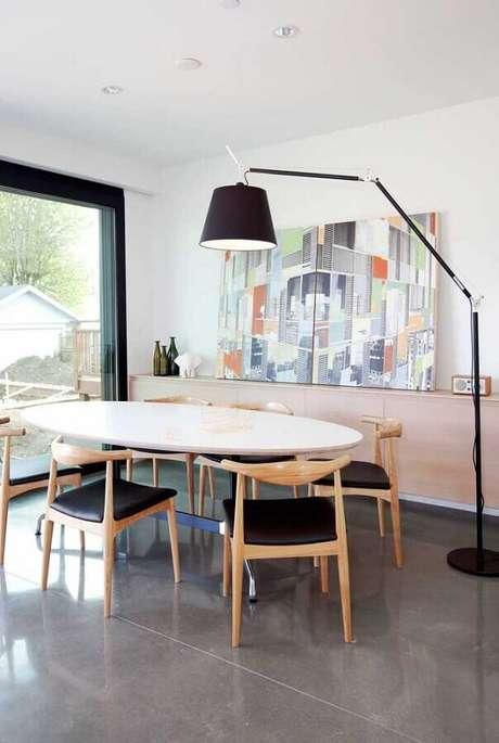 20. Abajur de pé para sala de jantar decorada com mesa oval e quadro grande – Foto: Futurist Architecture
