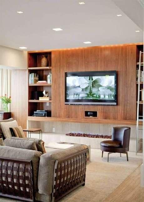 5. Decoração de sala com lareira ecológica grande e painel de madeira – Foto: Studio1202