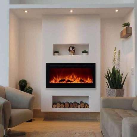 9. Decoração clean para sala com lareira elétrica e vasos de plantas – Foto: Pinterest