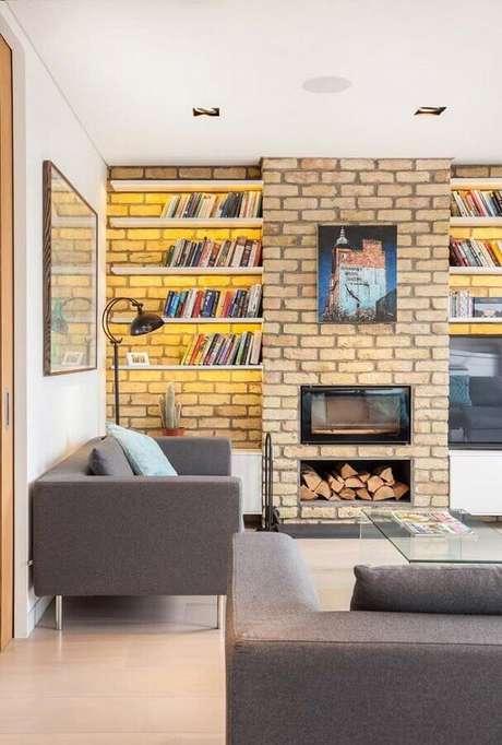 47. Sala com lareira decorada com prateleiras para livros e revestimento tijolinho – Foto: Houzz