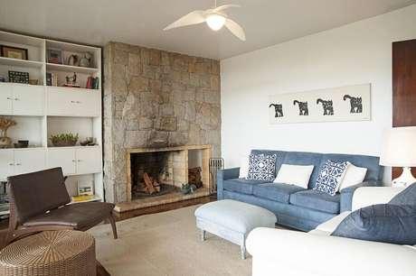 50. Sala com lareira rústica decorada com sofá azul – Foto: Renata Romeiro
