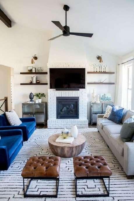 39. Poltrona azul para decoração de sala branca com lareira rústica – Foto: Arquitrecos