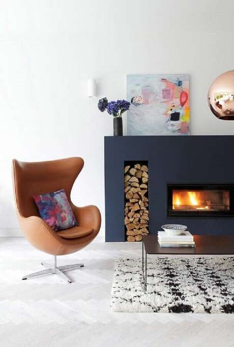 23. Sala com lareira decorada com poltrona de couro marrom – Foto: Houzz