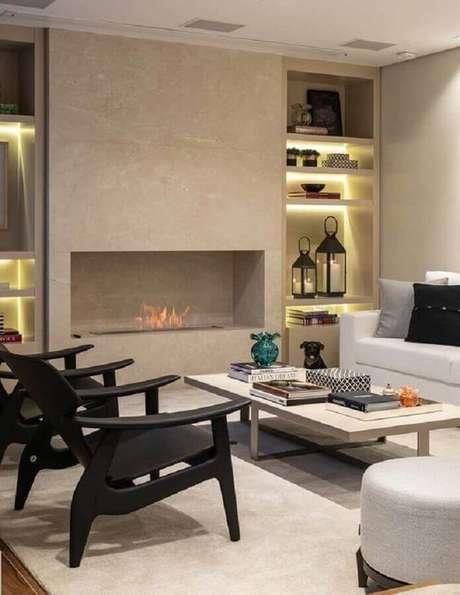 3. Sala de estar com lareira a gás decorada com poltronas pretas modernas – Foto: Casa de Valentina