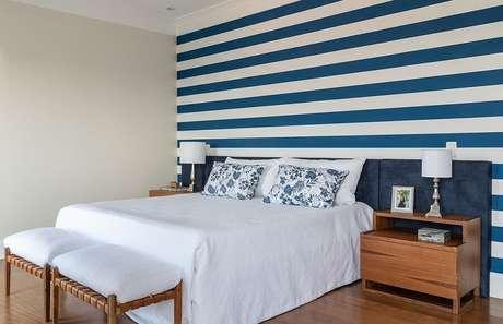 4. Decoração de quarto de casal com cabeceira colorida azul estofada e papel de parede listrado – Foto: habitissimo
