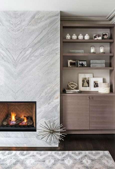 43. Revestimento de mármore para decoração sofisticada de sala com lareira – Foto: Jeito de Casa