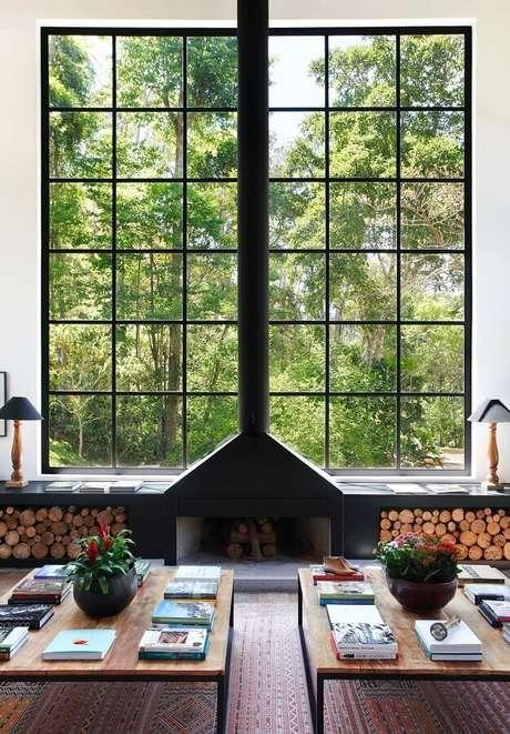 52. Sala de estar com lareira rústica decorada com amplas janelas – Foto: Home Fashion Trend