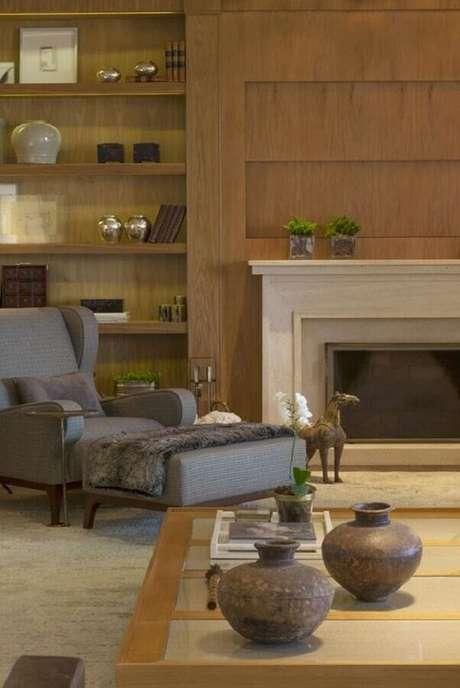 46. Sala com lareira decorada com poltrona cinza e prateleiras de madeira – Foto: Casa Tres Chic