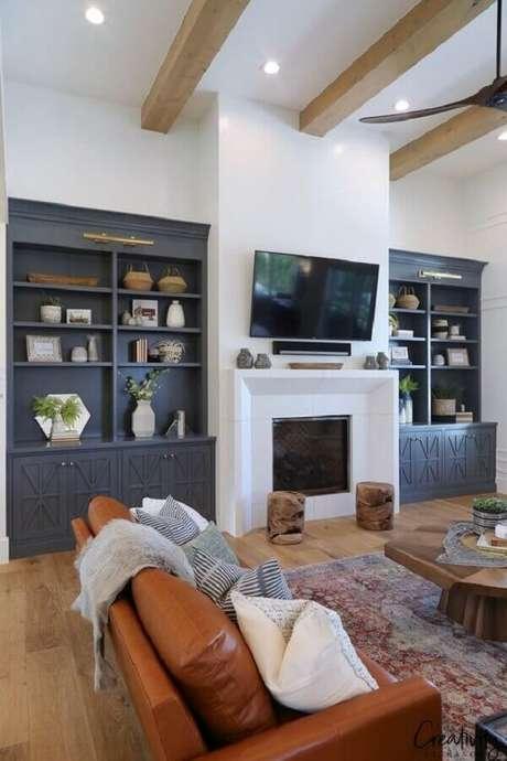 55. Sofá de couro para decoração de sala com lareira e estantes cinza – Foto: Behance