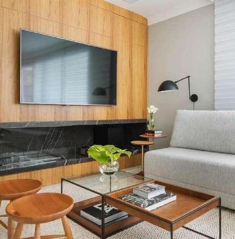 48. Sala com lareira grande decorada com sofá cinza sem braço e revestimento de madeira – Foto: Pinterest