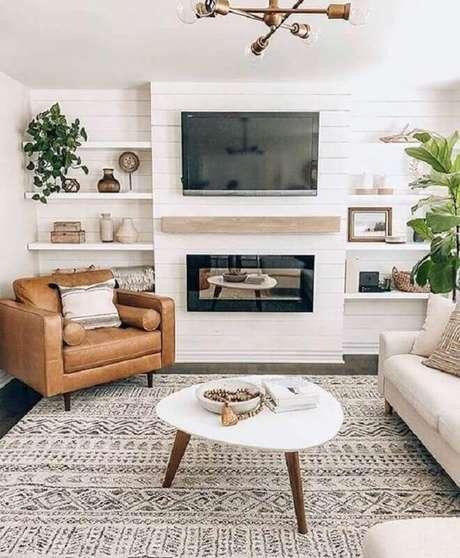 14. Cores claras para sala com lareira decorada com poltrona de couro marrom – Foto: Monarch Plank